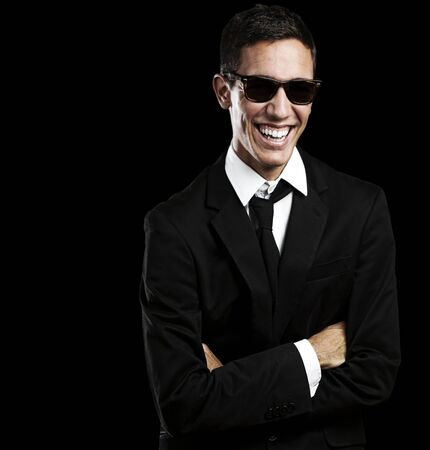 portrait of business young man with sunglasses smiling against a black background photo