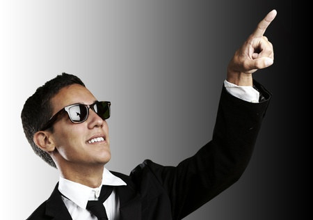 portrait of handsome young man with sunglasses pointing up against a black background photo