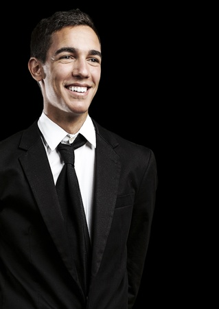 portrait of young business man smiling against a black background photo