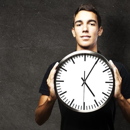 portrait of young man holding a clock against a grunge wall photo