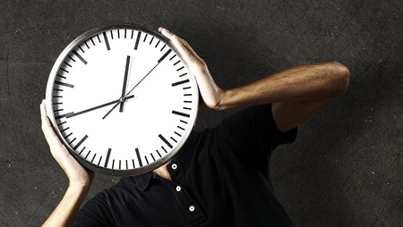 portrait of young man holding a clock against a grunge background Stock Photo - 10973832