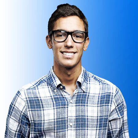 portrait of young man with shirt and glasses over a blue background photo