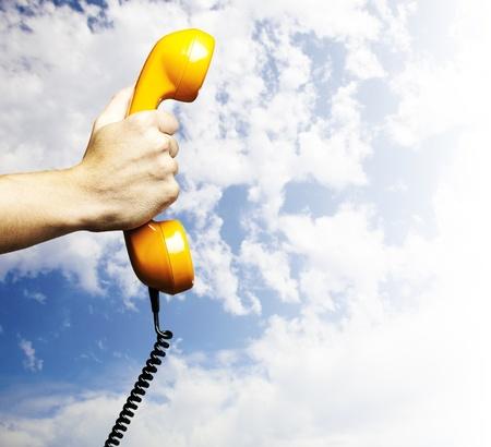 main tenant un téléphone millésime sur un fond bleu ciel