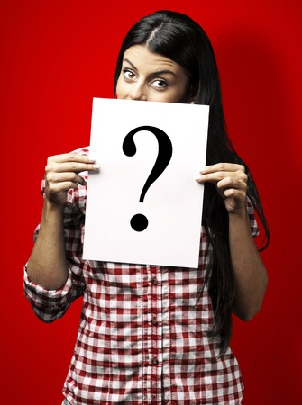 portrait of young woman with question paper on red background photo