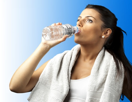 portrait of young woman with towel drinking water against a blue background photo