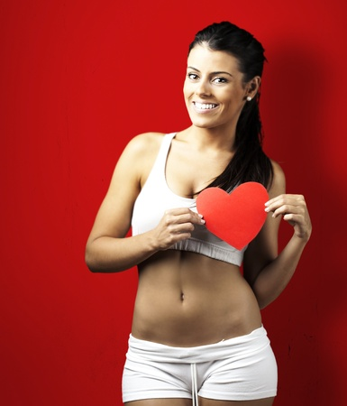 healthy body: portrait of healthy young woman with red heart over red