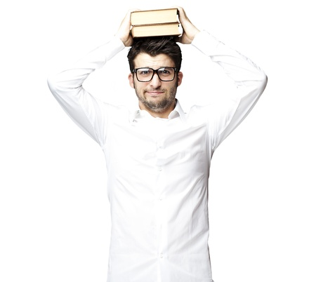 portrait of young man with glasses holding books on his head over white background photo