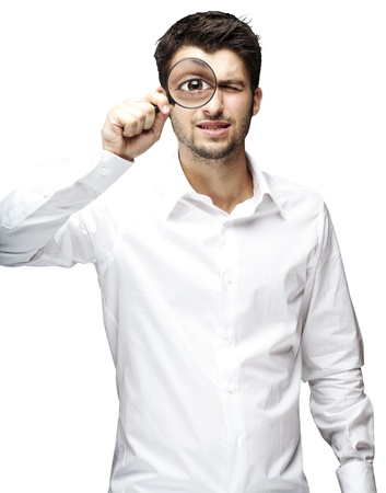 portrait of young man looking through a magnifying glass over white background photo