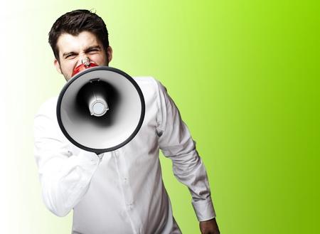 jefe enojado: retrato de hombre joven con megáfono gritando sobre fondo verde