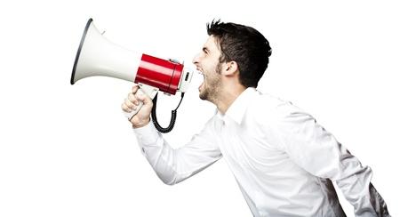 exitacion: Retrato de hombre joven y guapo gritando con el megáfono sobre fondo negro Foto de archivo