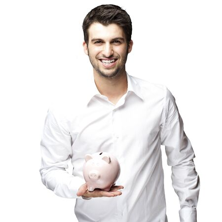 portrait of young man smiling and holding a piggy bank against a black background Stock Photo - 11506303