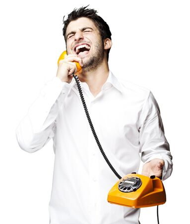 portrait of young man talking using vintage telephone laughing over white background photo