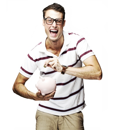 portrait of crazy man saving money in piggy bank against a white background photo