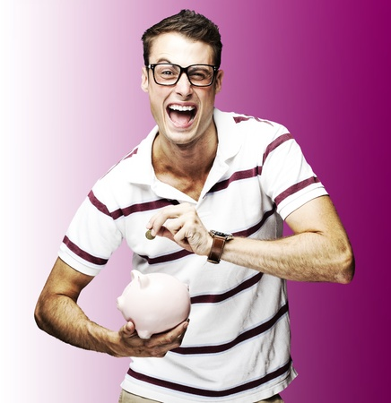 portrait of crazy man saving money in piggy bank against a pink background photo
