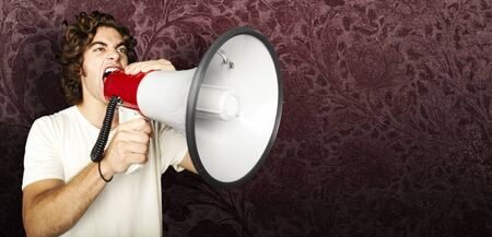 portrait of young man shouting with megaphone against a grunge background Stock Photo - 11506397