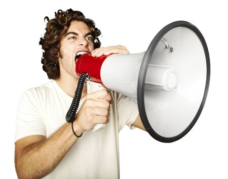 crazy man: portrait of young man shouting with megaphone over white background