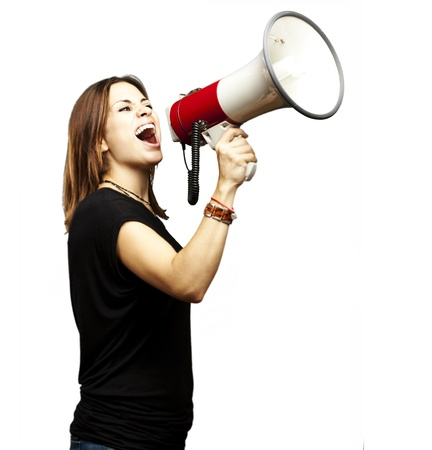 portrait of young girl shouting with megaphone over white background photo