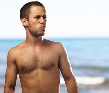 nue plage: jeune homme sur un fond de plage Banque d'images
