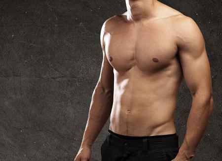 desnudo masculino: hombre joven y sano sobre un fondo grunge Foto de archivo