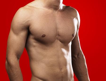 desnudo masculino: hombre joven y sano sobre un fondo rojo