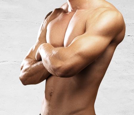 sterke torso van de jonge man tegen een stenen muur