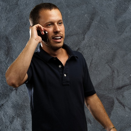 young man talking on mobile phone against a grunge background photo
