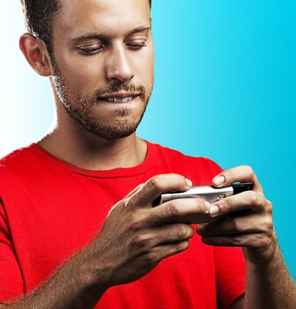 young man typing on mobile phone on blue background photo