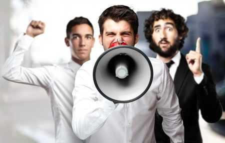 portrait of employees group shouting using a megaphone against a city background photo