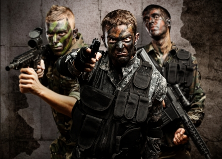 group of soldiers aiming with rifles against a grunge bricks wall Stock Photo - 11506611