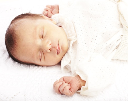 portrait of newborn baby sleeping in a bed ober white background photo