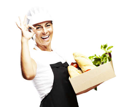 portrait of middle aged woman carrying groceries in a box over white photo