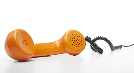 handset: vintage orange telephone handset over white background