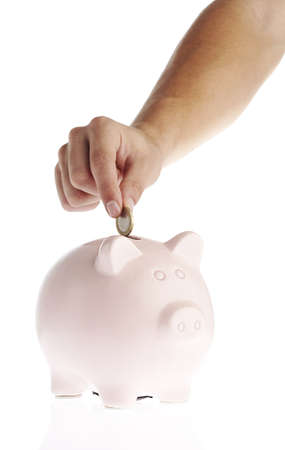 putting in: man putting money in piggy bank over white background Stock Photo