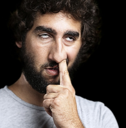 Portret van een jonge man met de vinger op zijn neus tegen een zwarte achtergrond Stockfoto