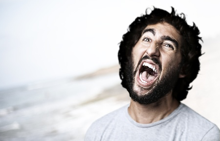 portrait of young man shouting against a beach background Stock Photo - 11507138