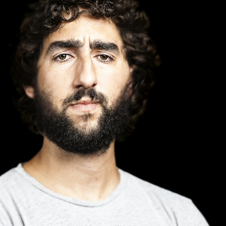 portret van een ernstige jonge man tegen een zwarte achtergrond Stockfoto