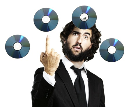 portrait of young man pointing up and cds flying over white Stock Photo - 11507095