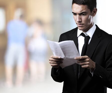 portrait of a handsome young business man reading a contract at a crowded place photo