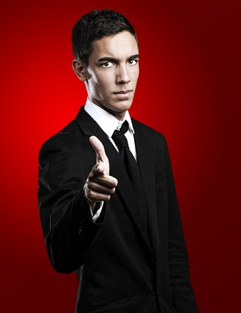 portrait of young business man pointing with suit against a red background photo