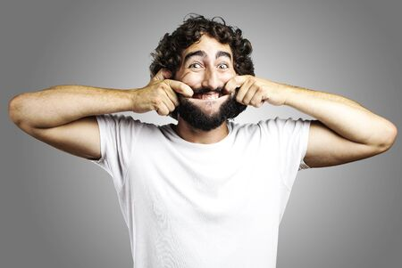 portrait of young man pulling his mouth smiling over grey background Stock Photo - 11507410