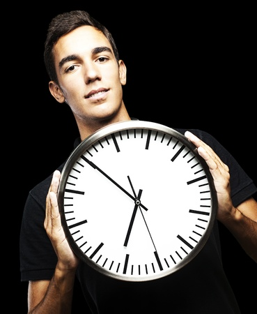 portrait of young man holding a clock with his hands over black background photo