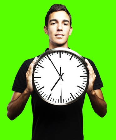 portrait of man holding clock against a removable chroma key background photo