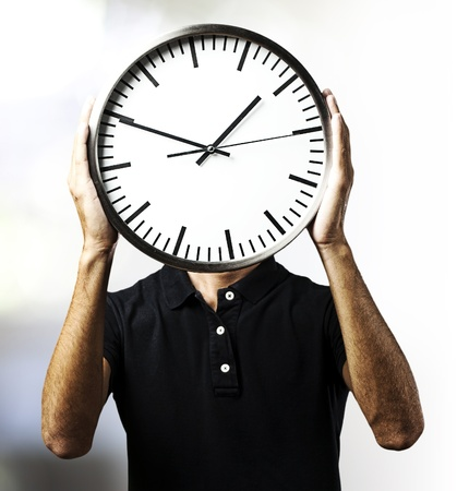 portrait of young man holding a clock with his hands against a abstract background photo