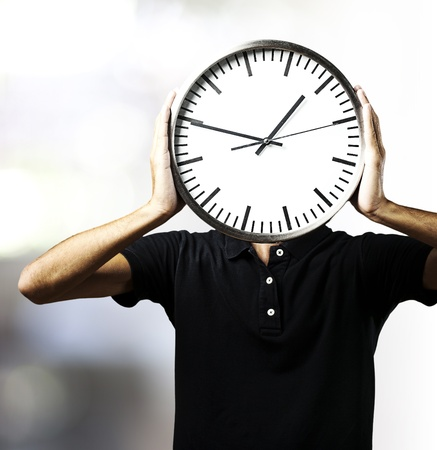 head home: portrait of young man holding a clock with his hands against a abstract background
