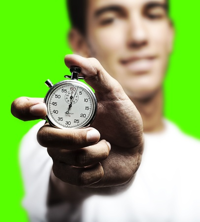 young man pushing a stopwatch buttton against a removable chroma key background photo