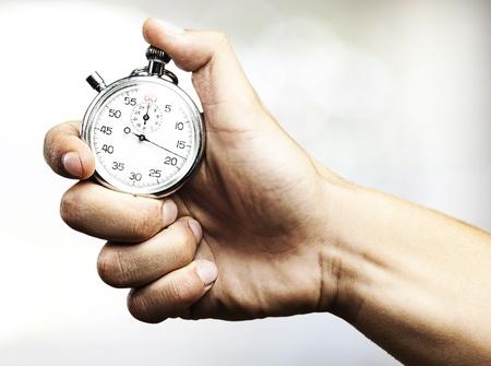 relógio: m�o que prende o cron�metro contra um fundo abstrato Imagens