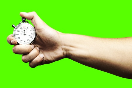 removable: hand pushing a stopwatch button to stop it against a removable chroma key background