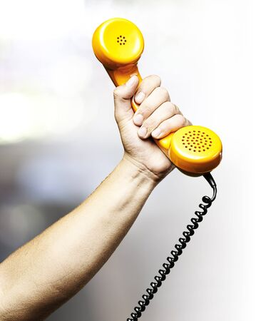hand holding a yellow vintage telephone indoor photo