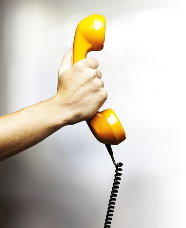 main tenant un téléphone jaune à l'intérieur millésime