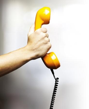 telefono antico: mano che regge una coperta gialla di telefono d'epoca